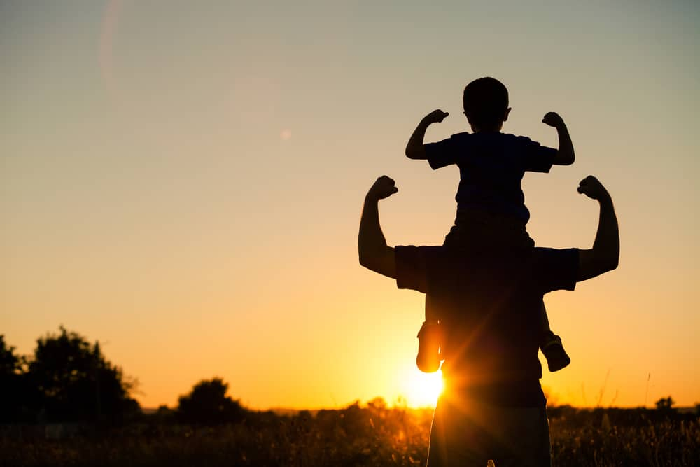 Ein Mann bei Sonnenuntergang hält seinen Sohn auf den Schultern