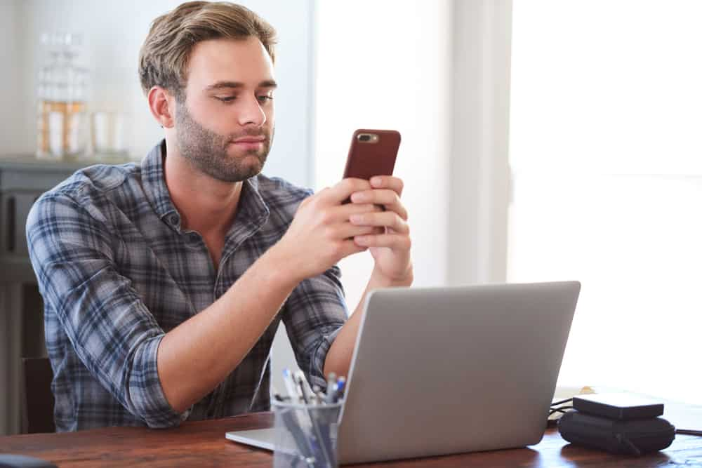 Ein Mann bei der Arbeit sitzt an einem Schreibtisch und flirtet über Nachrichten auf einem Handy