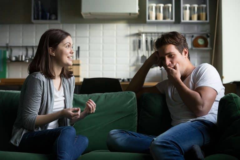 Ein Mann, der sich langweilt, während ein Mädchen ihm von seinem Tag erzählt