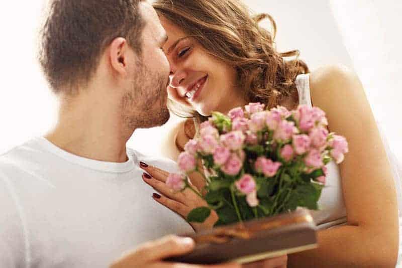 Ein Mann gibt einer lächelnden Frau einen Blumenstrauß und ein Geschenk