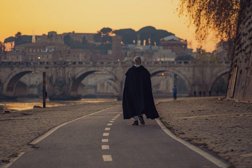 Ein Mann in einem schwarzen Umhang geht die Straße entlang