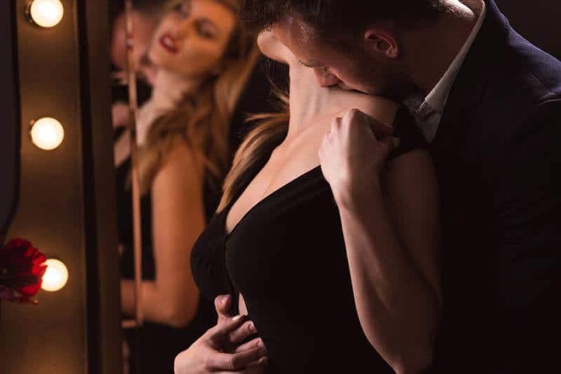 Ein Mann küsst leidenschaftlich den Hals einer Frau