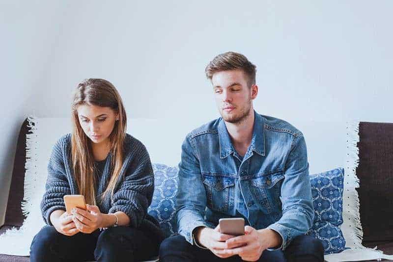 Ein Mann schaut in das Telefon seiner Frau