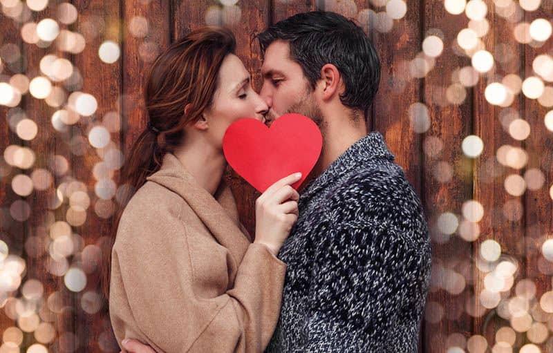 Ein Mann und eine Frau, die ein Herz in der Hand halten, stehen und küssen sich