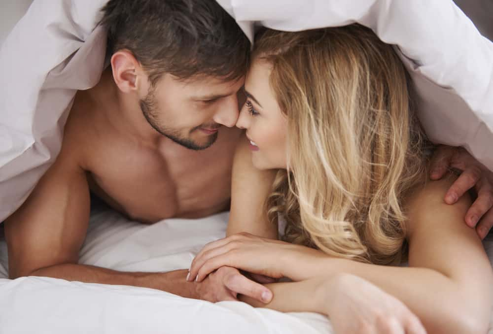 Ein Mann und eine Frau sehen sich unter einer weißen Decke an