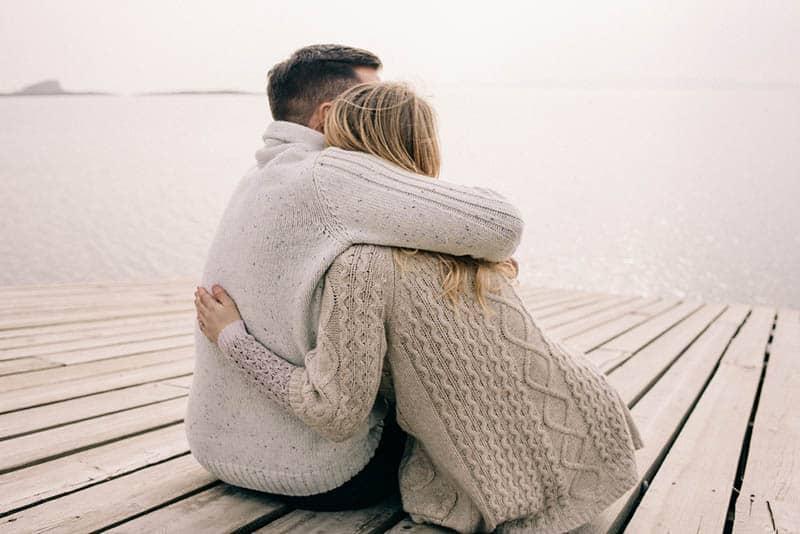 Ein Mann und eine Frau sitzen in einer Umarmung auf einem Pier am Meer