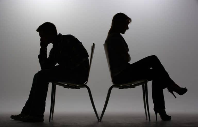 Ein Mann und eine Frau sitzen mit dem Rücken einander zugewandt