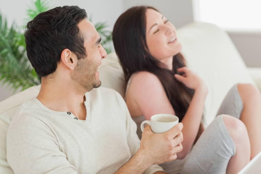 Ein Mann und eine lächelnde Frau sitzen auf der Couch und reden