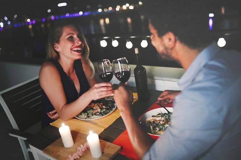 Ein Paar beim Abendessen in einem Restaurant, das mit Wein röstet