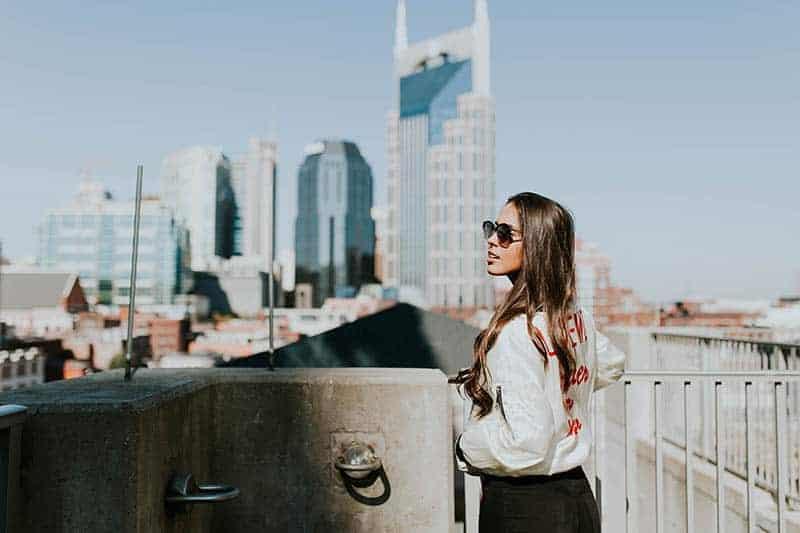 Ein attraktives Mädchen mit Sonnenschirmen steht am Tor
