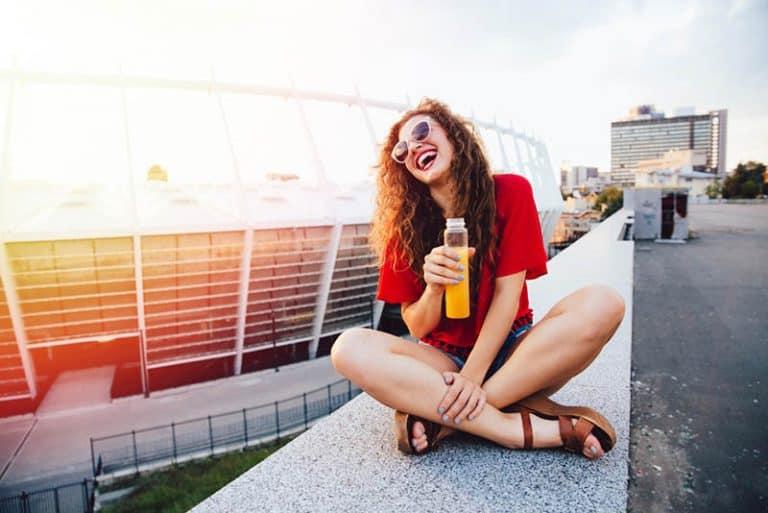 Ein fröhliches Mädchen sitzt an der Wand und trinkt Saft