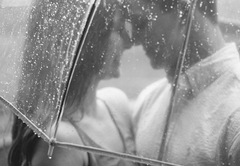Ein glückliches Liebespaar steht unter einem Regenschirm