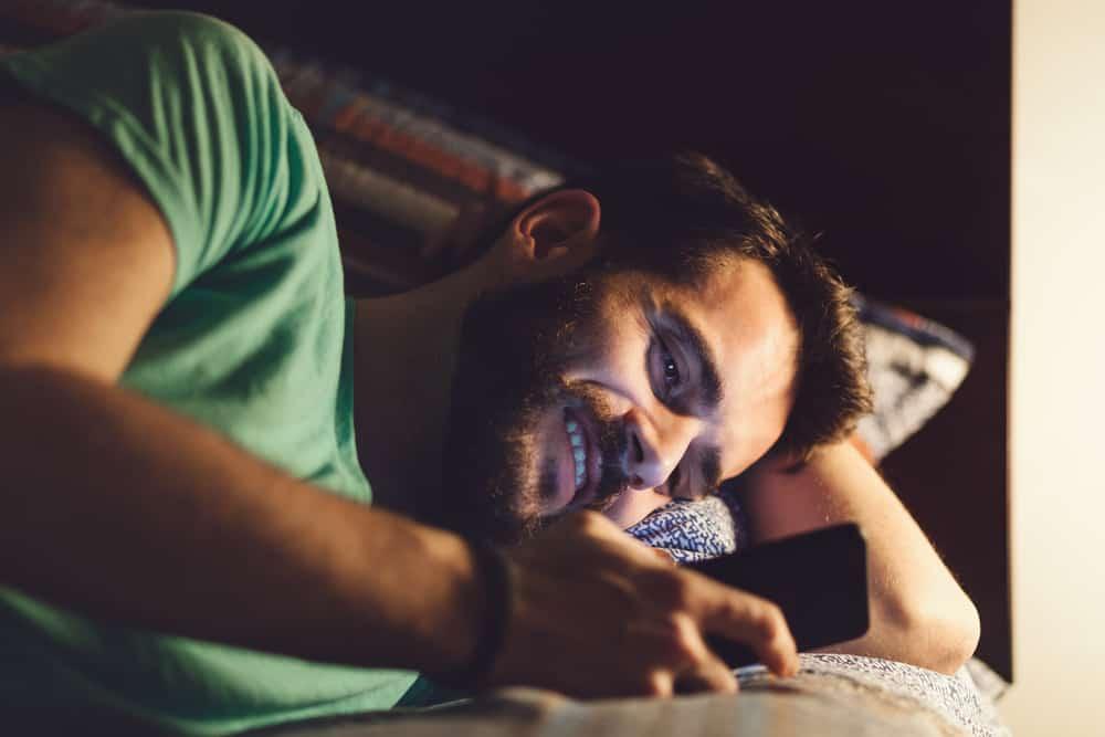 Ein junger Mann mit Bart in einem grünen T-Shirt liegt und benutzt das Telefon mit einem Lächeln