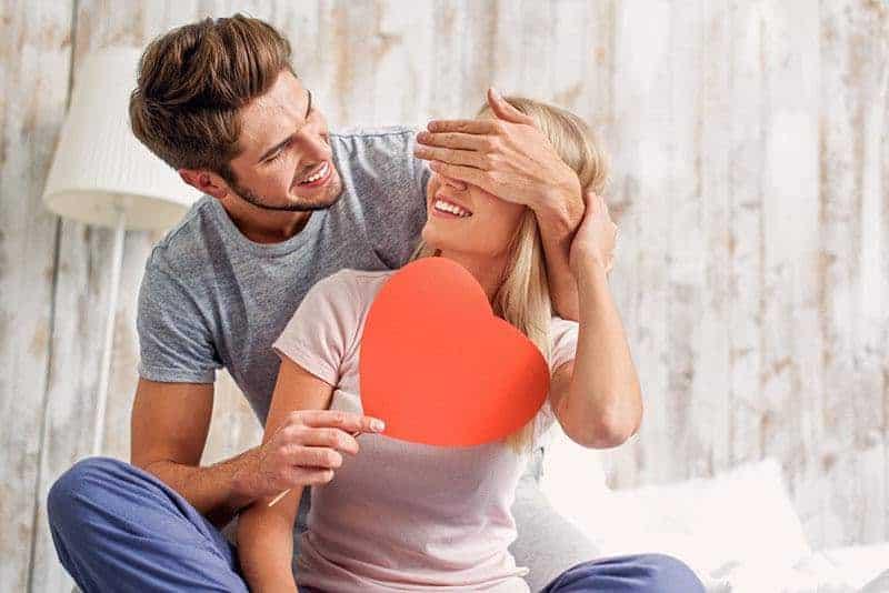 Ein lächelnder Mann gibt seiner Frau ein Herz