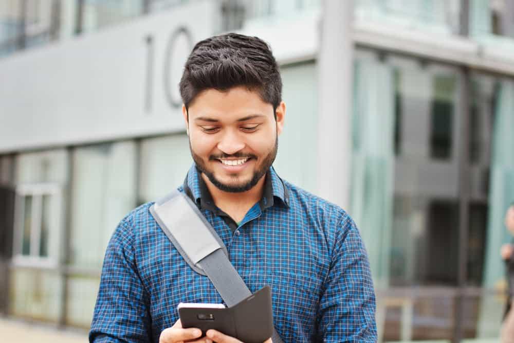 Ein lächelnder Mann mit Bart in einem blauen Hemd liest eine SMS auf seinem Handy