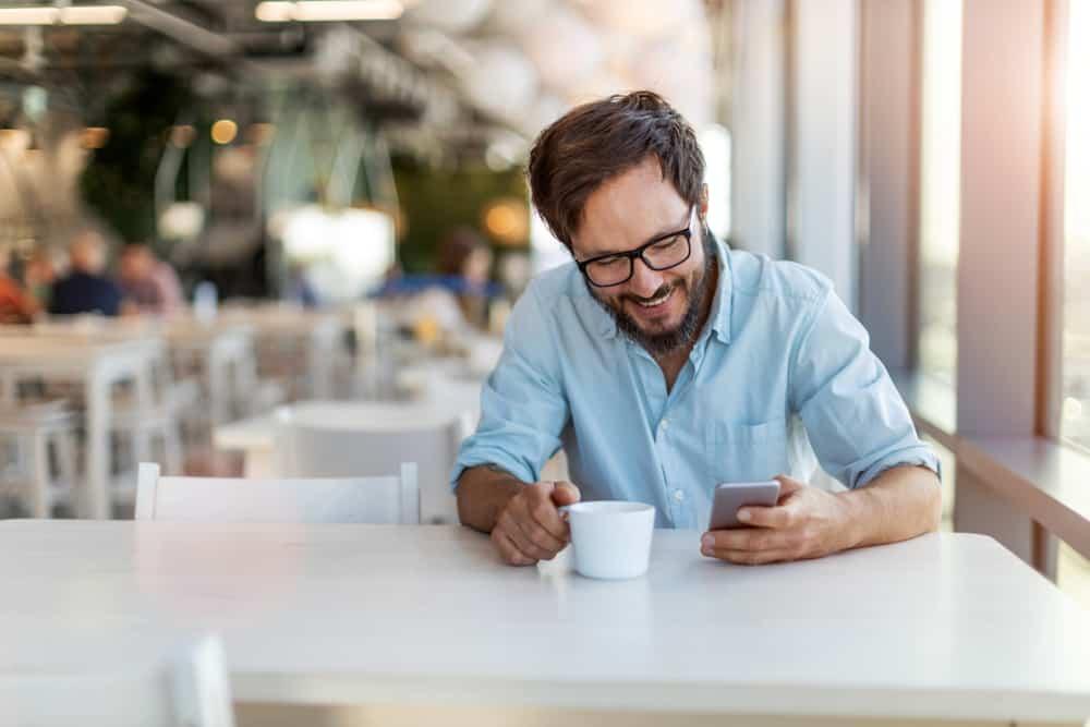 Ein lächelnder Mann mit Bart und Brille liest eine Nachricht auf seinem Handy und trinkt Kaffee