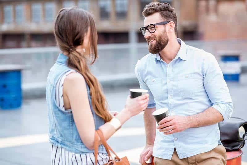 Ein lächelnder Mann mit Bart und eine Frau, die auf der Straße Kaffee trinkt
