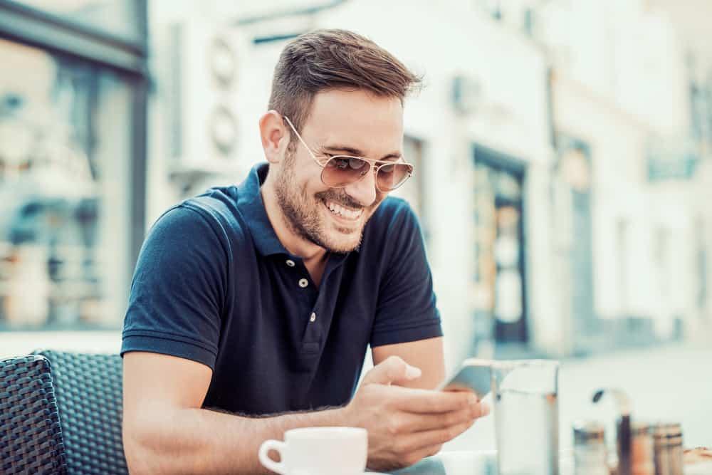 Ein lächelnder Mann mit Sonnencreme sitzt auf der Terrasse eines Cafés und benutzt ein Handy