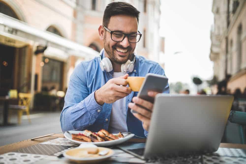 Ein lächelnder Mann mit einem Telefon in der Hand frühstückt auf der Restaurantterrasse