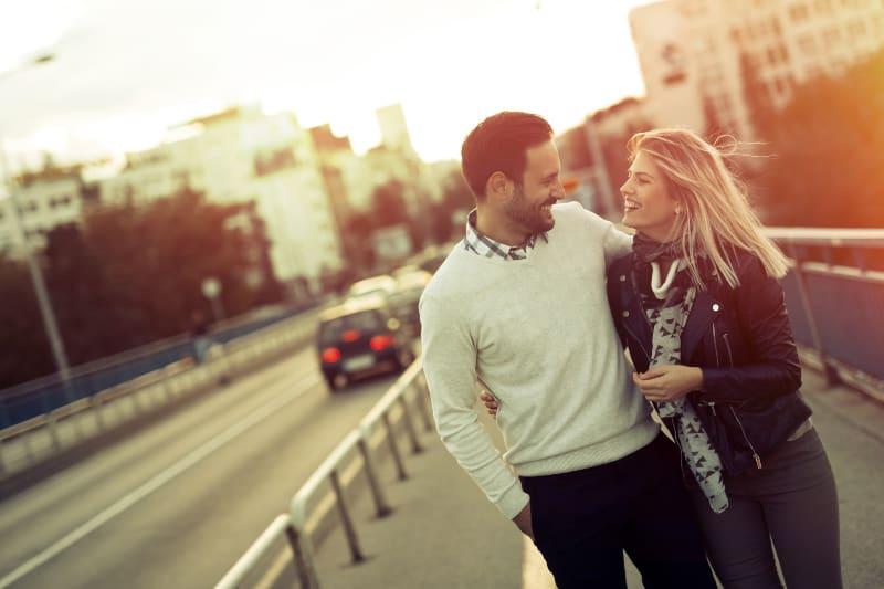 Ein liebevolles Touristenpaar geht umarmend die Straße entlang
