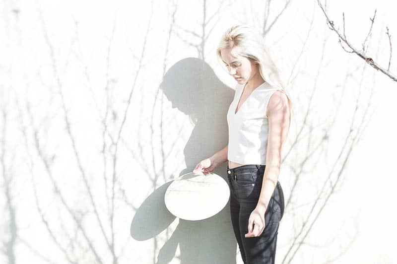 Eine Blondine in einem weißen T-Shirt und einer schwarzen Hose steht draußen mit einem Spiegel in der Hand