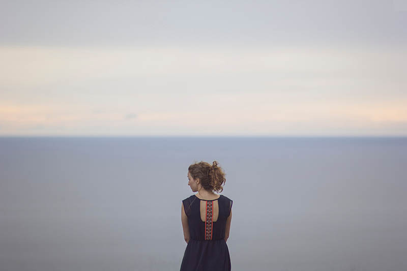Eine Brünette in einem ungewöhnlichen Kleid steht am Meer