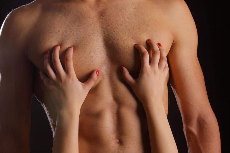 Eine Frau berührt einen Mann auf der Brust