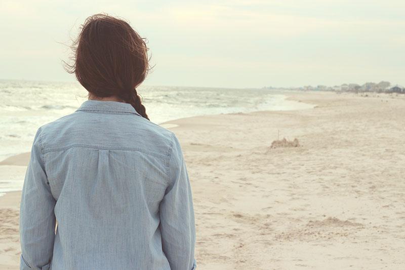 Eine Frau in Jeansjacke steht an einem Sandstrand und beobachtet das Meer