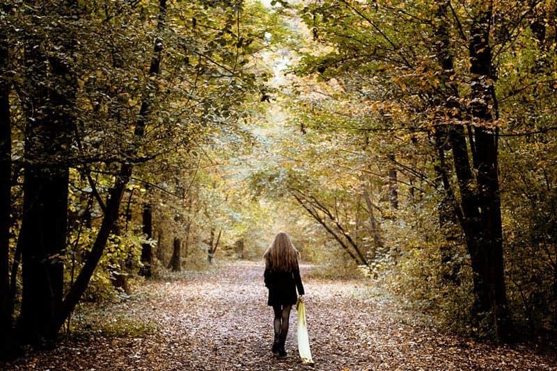 Eine Frau in Mantel und Minirock geht durch den Wald
