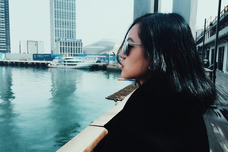 Eine Frau mit Sonnenbrille sitzt in einem Bootshafen