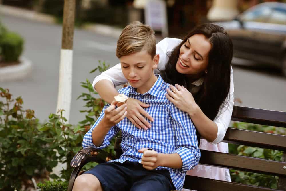 Eine Mutter umarmt ihren Sohn hinter ihrem Rücken, der auf einer Bank sitzt und Eis isst