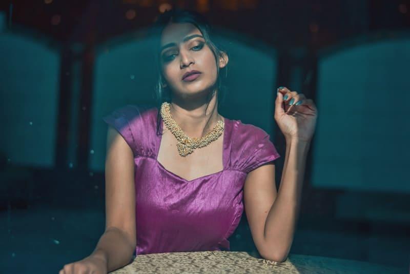 Eine attraktive Frau in einem lila Kleid sitzt