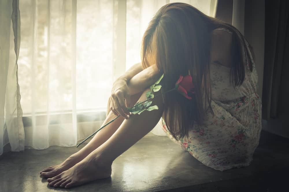 Eine barfüßige traurige Frau in einem Kleid mit einer Rose in der Hand sitzt am Fenster