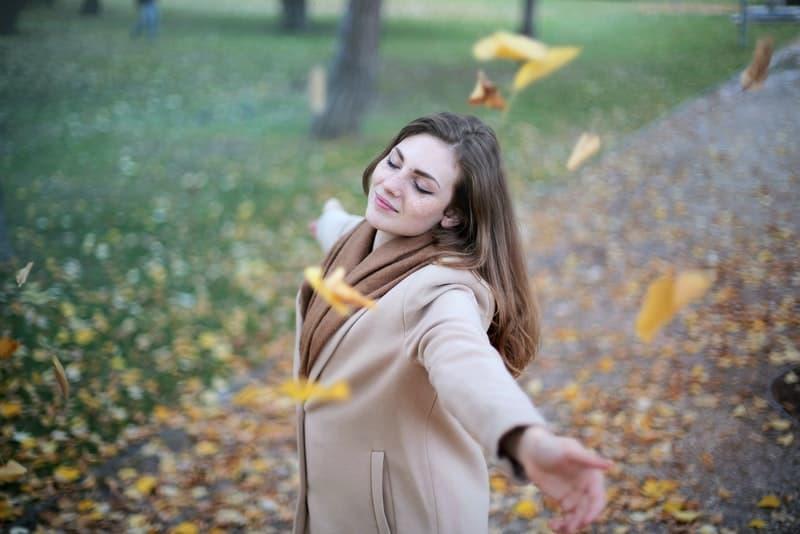 Eine fröhliche Frau mit ausgestreckten Armen genießt die Brise