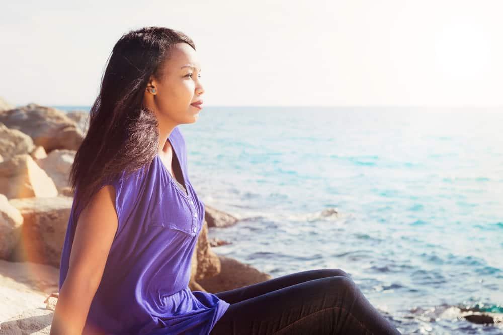 Eine schöne schwarze Frau in einem lila T-Shirt sitzt am Strand
