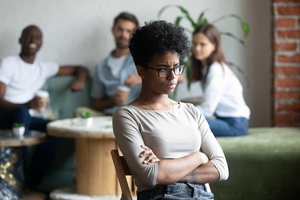 Eine wütende schwarze Frau sitzt vor lächelnden Menschen