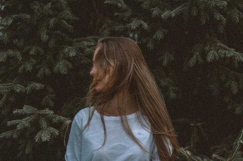 Frau, die weißes Hemd nahe Baum trägt