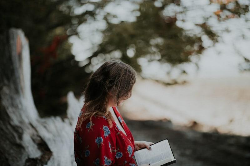 Frau hält Buch am Strand