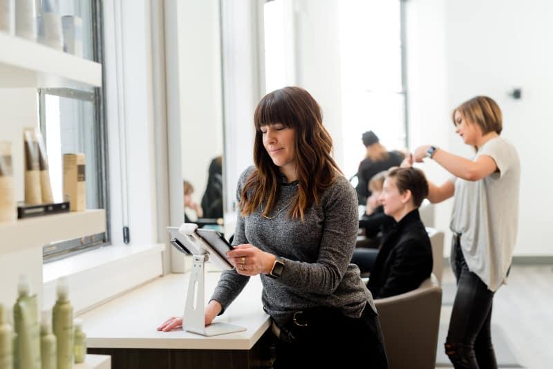 Frau im grauen Pullover, der Tablet-Computer hält