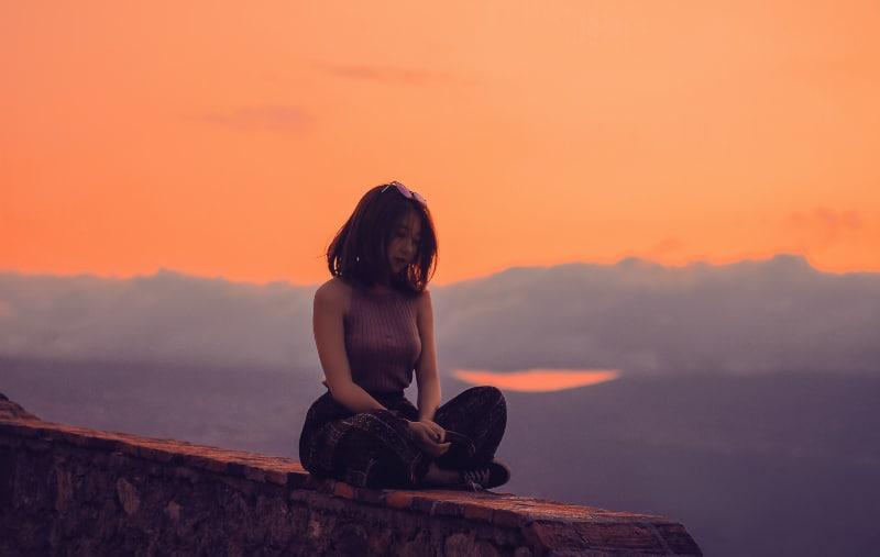 Frau sitzt auf einer Klippe