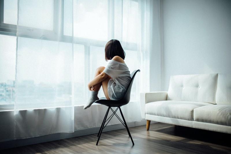 Frau sitzt auf schwarzem Stuhl vor Glasscheibe mit weißen Vorhängen
