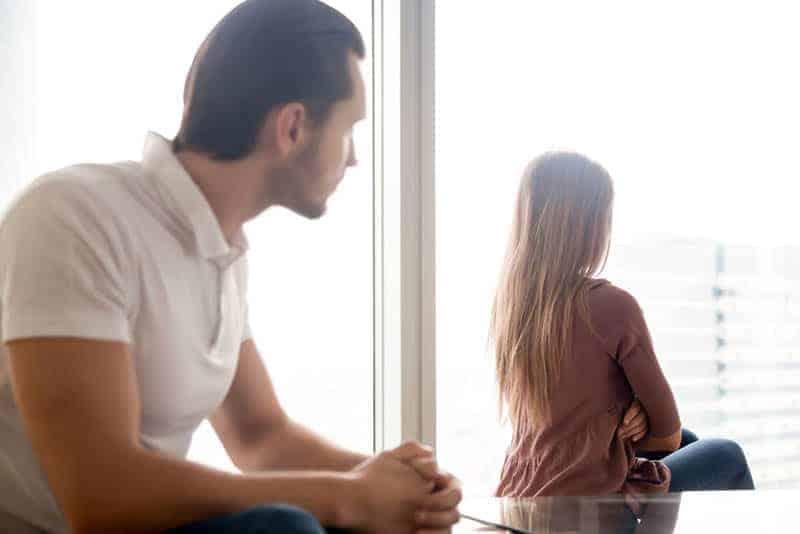 Frau sitzt gegen Mann