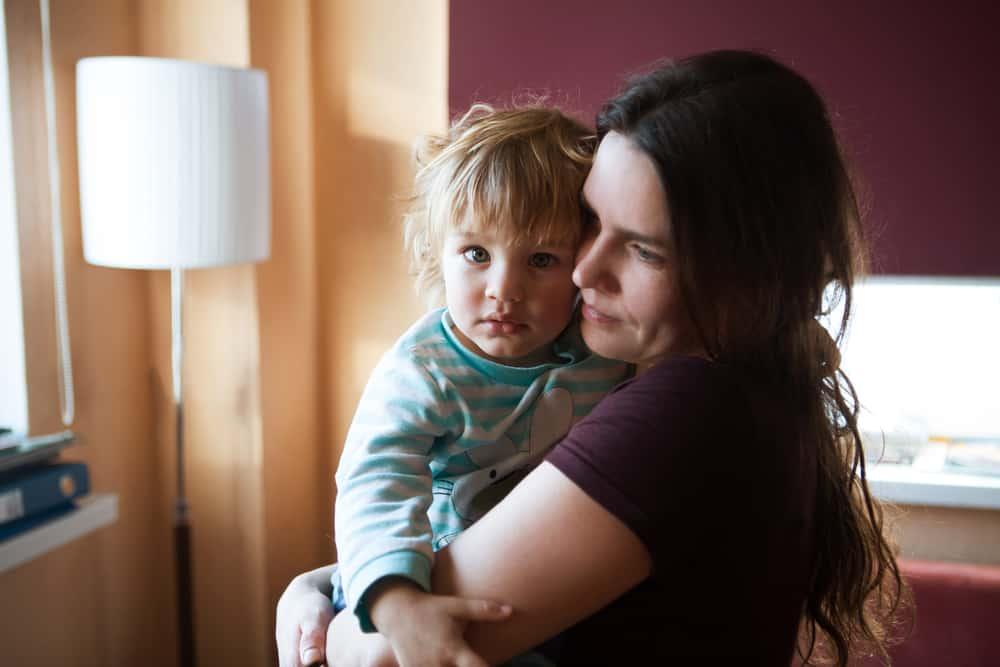 Im Haus steht eine Mutter mit einem Kind im Arm
