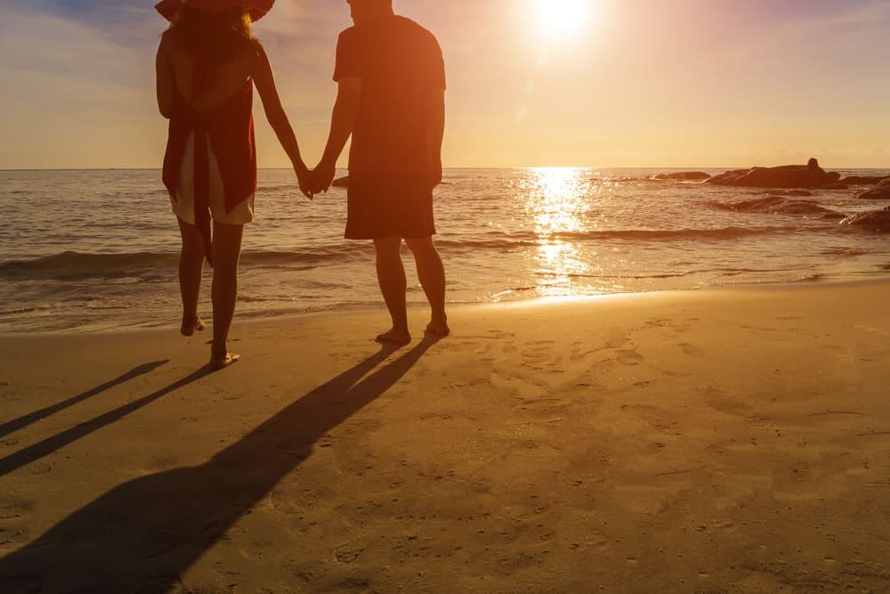 Liebespaar, das am Strand Händchen haltend steht