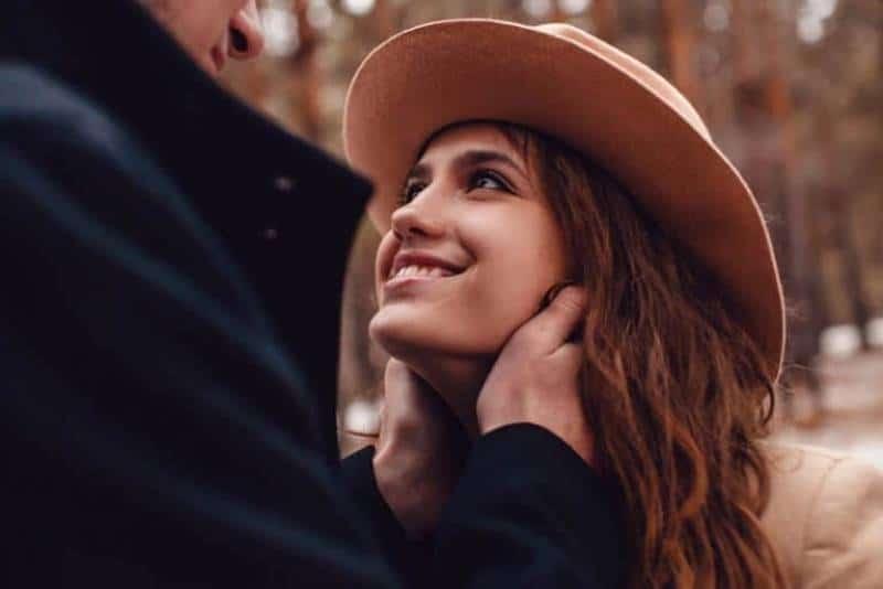 Mädchen mit Hut sieht ihren Freund mit einem Lächeln an