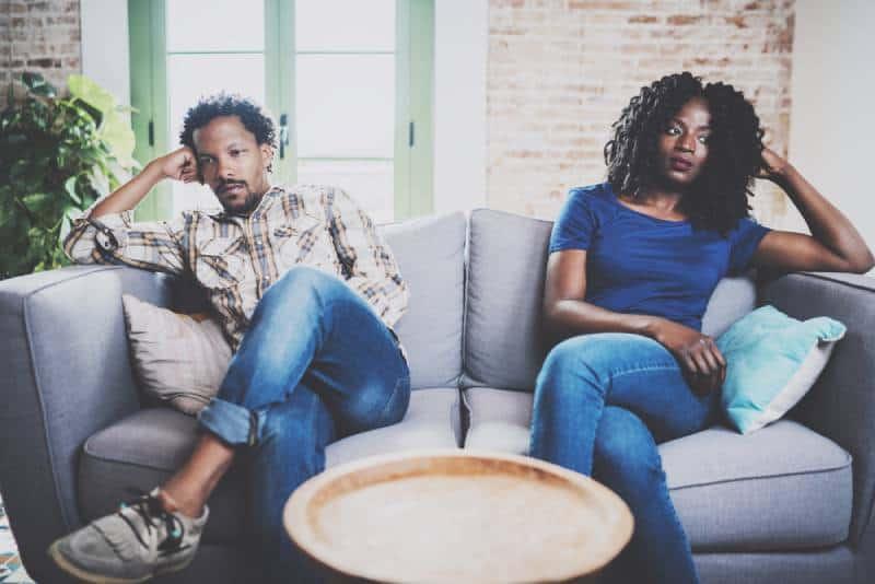 Männer streiten sich mit seiner Freundin, die neben ihm auf der Couch sitzt