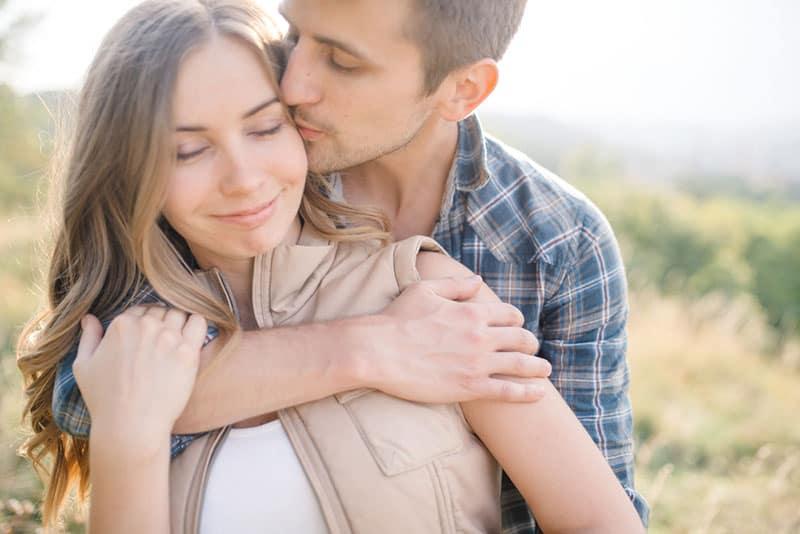 Mann küsst und umarmt lächelnde Frau in der Natur