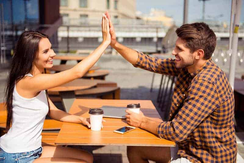 Mann und Frau High Five im Straßencafé