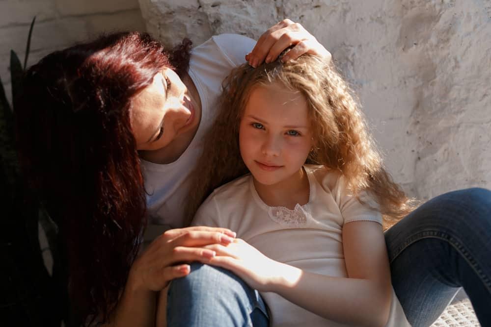 Mutter und Tochter sitzen in einer Umarmung