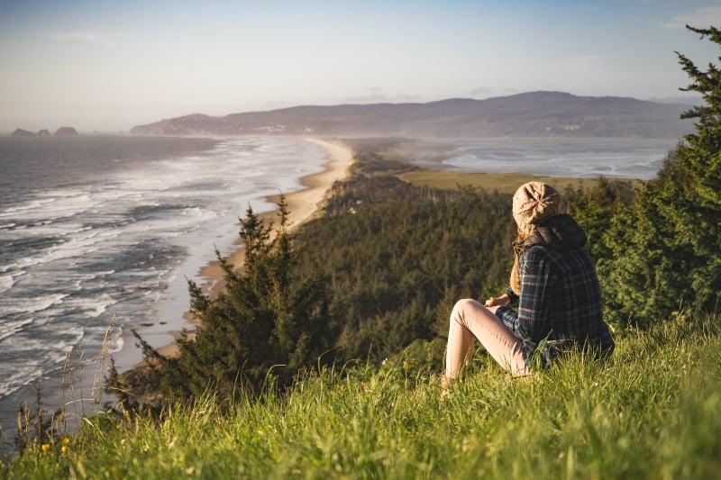 Person, die auf Hügel nahe Ozean während des Tages sitzt